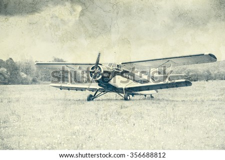 Taking off the old retro plane from the meadow. Vintage style image. - stock photo