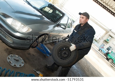 taking off tyre from car for repair work (replacement) - stock photo