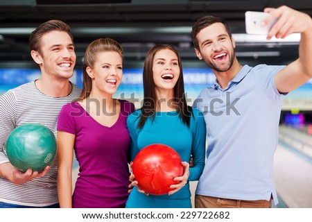 Taking photo before starting the game. Cheerful friends making selfie while standing against bowling alleys  - stock photo