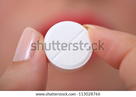 Taking pills Close-up of a white pill in woman's fingers. - stock photo