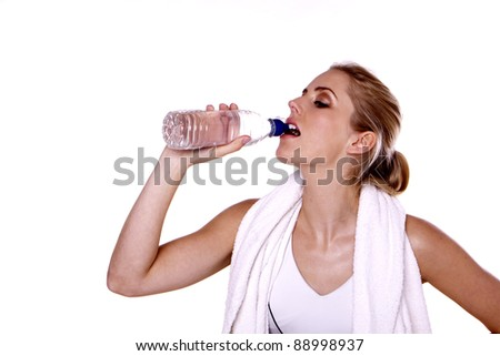 Taking refreshment. A young blond woman drinking water after a hard workout.
