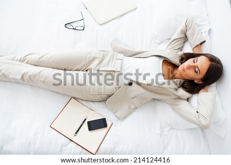 Taking rest hard working day. Top view of beautiful young businesswoman in suit holding hands behind head and keeping while lying in bed at the hotel room  - stock photo