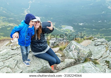 Taking selfie! Happy mother and baby boy making self portrait in the mountains. Woman holding smartphone camera to take picture. Kasprowy Wierch (peak). Poland. Travel, technology concept. Copy space. - stock photo