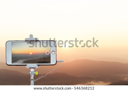 taking selfie of sunrise - hand hold monopod with mobile phone with blur of sunrise background