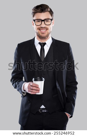 Taking time for coffee break. Confident young charming man in formalwear and eyeglasses holding coffee cup and smiling while standing against grey background - stock photo