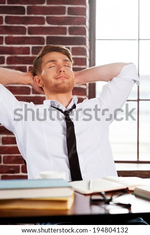 Taking time to relax. Handsome young man in shirt and tie holding keeping eyes closed and holding hands behind head while sitting at his working place  - stock photo