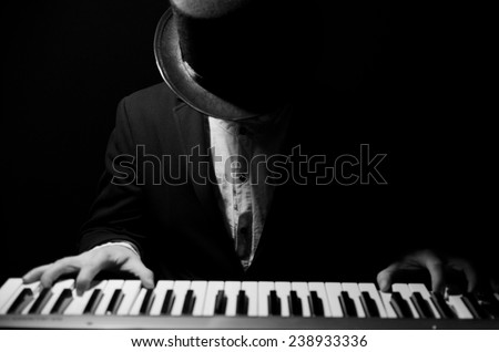 Talent and virtuosity. Black and white top view image of man playing piano - stock photo