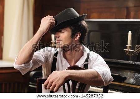 Talented and creative. Portrait of handsome young men sitting in front of his piano with closed eyes - stock photo