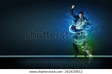 Talented cheerful businessman jumping with glowing energy lines on background - stock photo