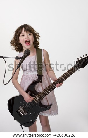 Talented musician can play the electic guitar and sing at the same time. Happy girl is singing with beautiful smile and fire in her eyes. Sincere emotion of joy.