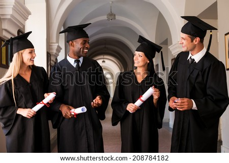 Talking about bright future. Four college graduates in graduation gowns walking along university corridor and talking - stock photo