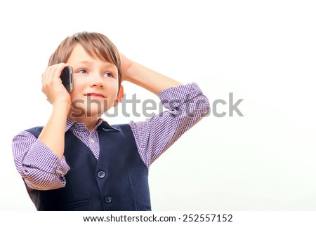 Talking about business. Cheerful little boy in formalwear talking on the mobile phone and holding hand over head while standing isolated on white - stock photo