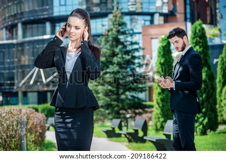 Talking by mobile phone. Successful business woman speaks by mobile phone. Businessman standing on the background and working on tablet - stock photo