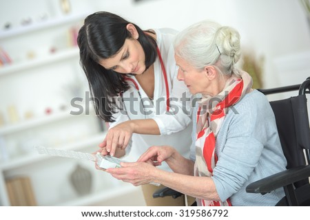 Talking old lady through her medication - stock photo