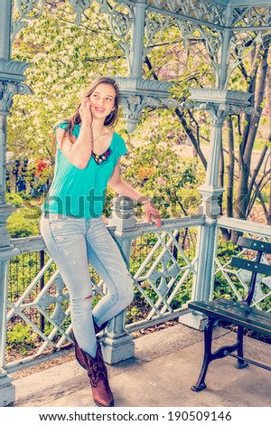 Talking on Phone. Dressing in a blue sleeveless top, fashionable jeans, brown boots, a blonde teenage girl is standing inside a pavilion, calling on her cell phone. Instagram Nashville effect.  - stock photo
