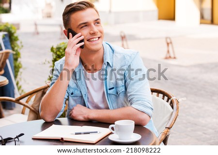 Talking with friends. Confident young man talking on the mobile phone and smiling while sitting in sidewalk cafe - stock photo