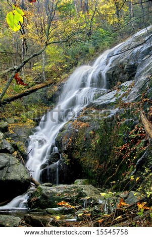 Tall and beautiful waterfall in the middle of autumn. - stock photo