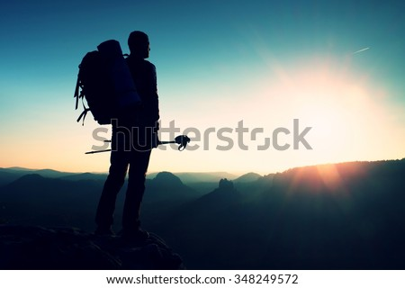 Tall backpacker with poles in hand. Sunny spring daybreak in rocky mountains. Hiker with big backpack stand on rocky view point above misty valley. Hiker watching blue daybreak. Hiking ambition. - stock photo