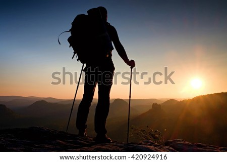 Tall backpacker with poles in hand. Sunny spring daybreak in rocky mountains. Hiker with big backpack stand on rocky view point above misty valley.