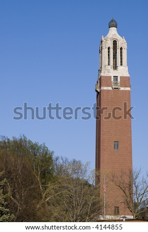 tall brick bell tower on right side with trees on left