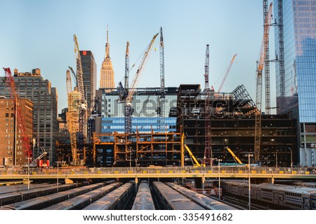 tall buildings under construction and cranes under a blue sky in New York City - stock photo