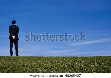 Tall business man outdoors looking off into the distance - stock photo