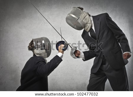 Tall businessman fencing with a smaller one - stock photo