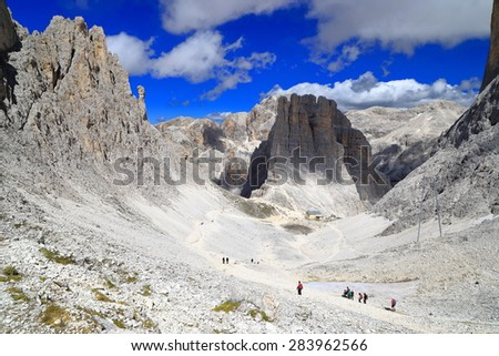 Tall cliffs surrounding deep valley in Catinaccio massif, Dolomite Alps, Italy - stock photo