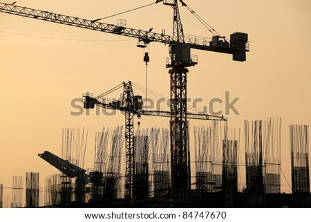 tall condominium buildings under construction in makati city manila in the philippines cranes and reinforcing rods silhouetted against the  sunset