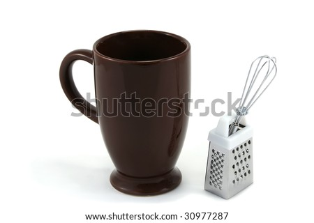 tall, dark brown ceramic mug for hot chocolate drink, with mini whisk and grater - stock photo