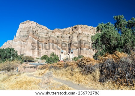 Tall dramatic cliffs standing behind a colonial church in the small town of Espicaya near Tupiza, Bolivia