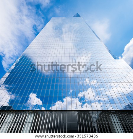 Tall glass building reflecting blue sky and white clouds during day