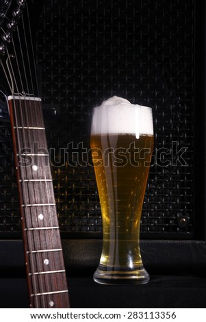 Tall glass full of light beer standing near a grilled music monitor with a guitar fretboard in the foreground - stock photo