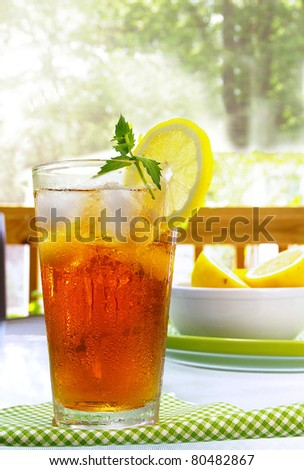 tall glass of cold iced tea with lemon and mint - stock photo