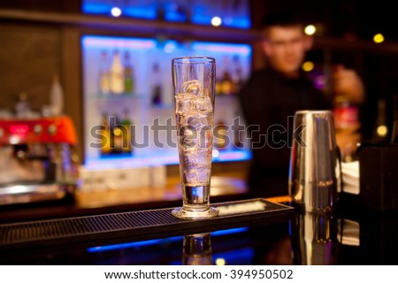 Tall glass with ice cubes on the bar counter. - stock photo
