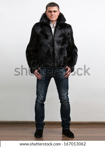 Tall handsome man wearing winter coat from natural beaver fur - stock photo