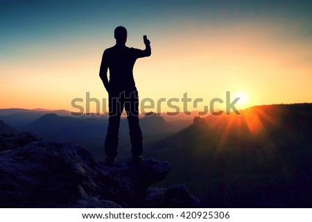 Tall man hiker is taking photo by smart phone on the peak of mountain at sunrise. - stock photo