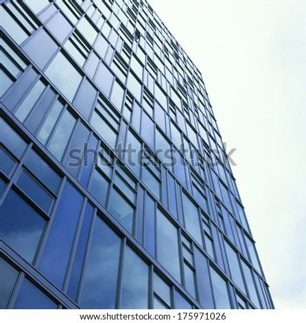 Tall, modern glass building against bright sky - stock photo