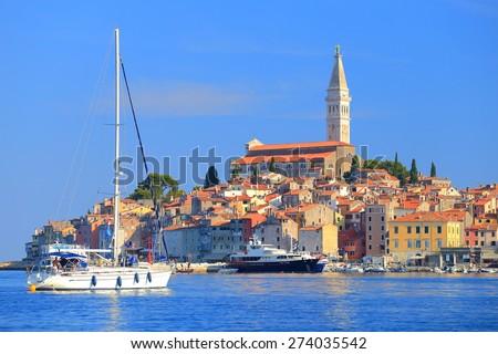 Tall sail boat enters the harbor of old Venetian town of Rovinj, Croatia - stock photo