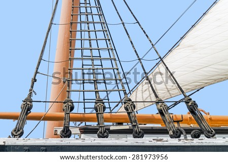 Tall ship rigging detail. Vintage sailing ship block and tackle, mast and sail  - stock photo