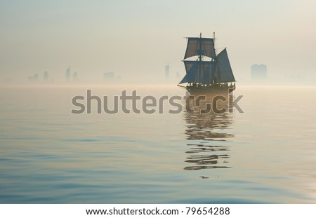 tall ship sailing into fog - stock photo