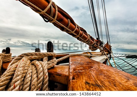 Tall ship schooner sailing on open water. Detailed close up of rigging, bow and boom and the textures of rope and wood. - stock photo