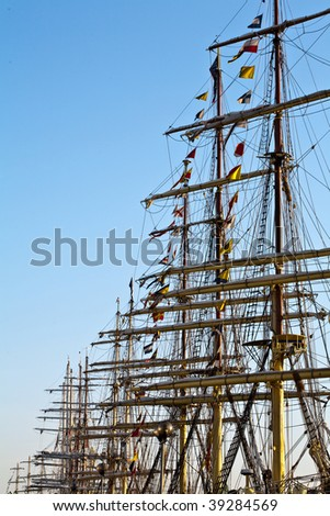 Tall ships masts in early morning clear sky - stock photo