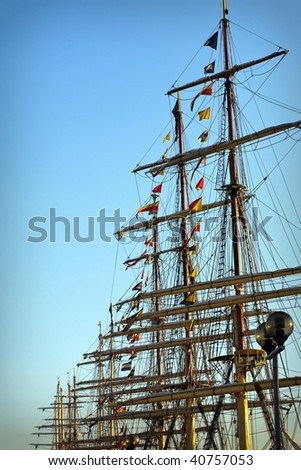 Tall ships masts in early morning clear sky