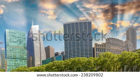 Tall skyscrapers over Bryant Park trees, Manhattan - New York City. - stock photo