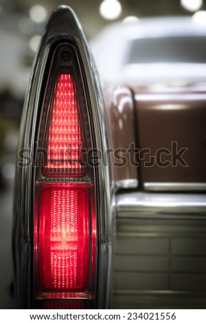 Tall thin pointed rear vintage tail light in the wing of an oldtimer classic motor car illuminated to show the red coloring, close up view. - stock photo