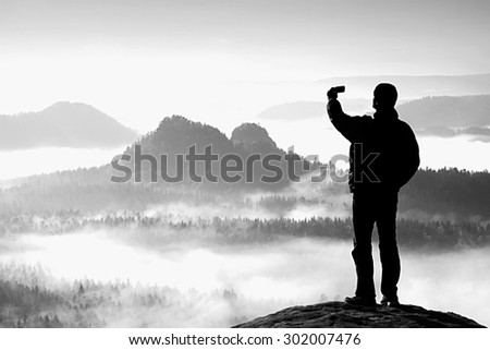 Tall tourist is taking selfie on peak above valley. Black and white photo - stock photo