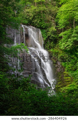 Tall Waterfall surrounded by green forest in summer - stock photo