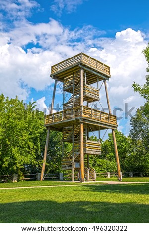 Tall wooden lookout tower for observing nature with elevated open air platforms connected by winding steps overlooking forest or woodland standing on neat green lawns