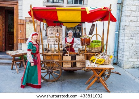 Tallinn, Estonia - June 2, 2016: Beautiful girls in national medieval dresses are selling nuts on a wooden cart in the Historical Center of Tallinn city. Tallinn, Estonia.